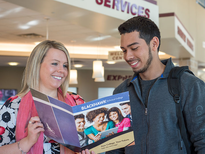 student and admissions member viewing college materials