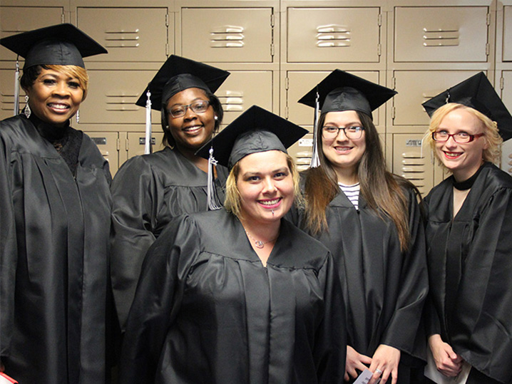 GED students standing in hallway wearing caps and gowns