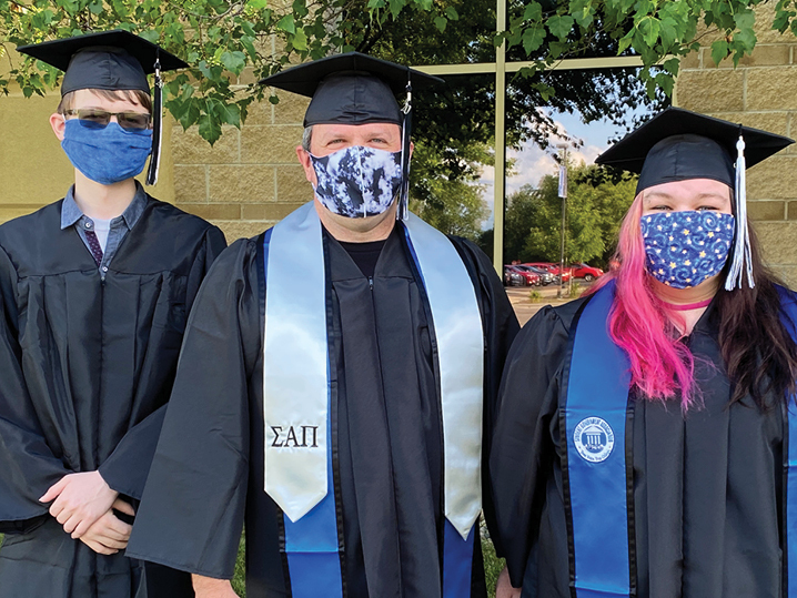 three graduates outside wearing caps, gowns, and masks