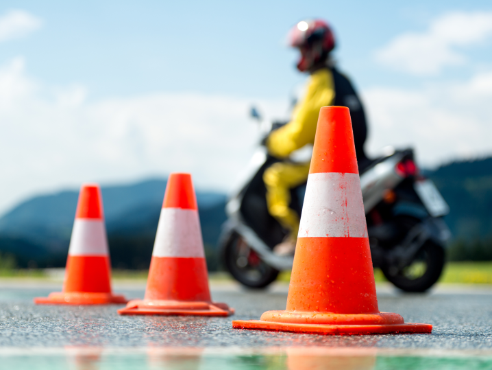 person riding motorcycle around safety cones