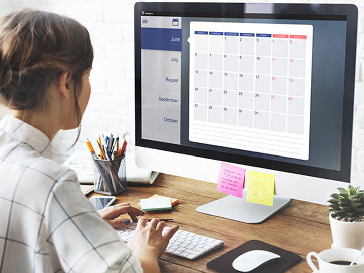 person looking at calendar on computer