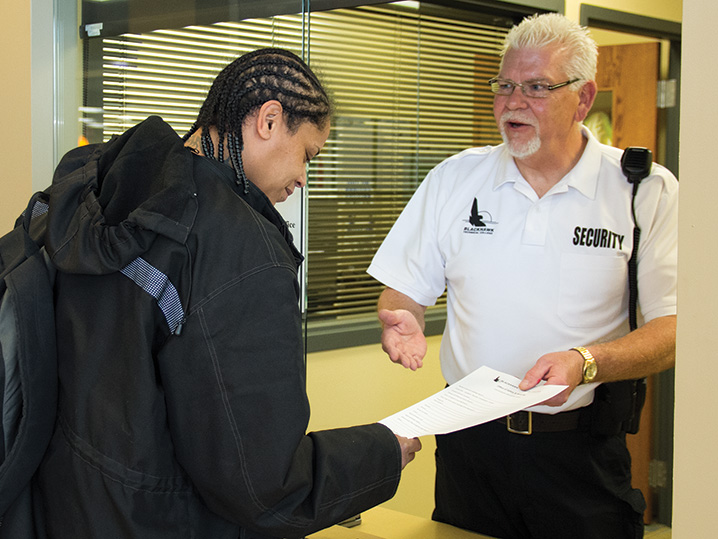 security officer handing paper to student