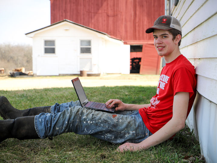 male student using laptop outside on farm