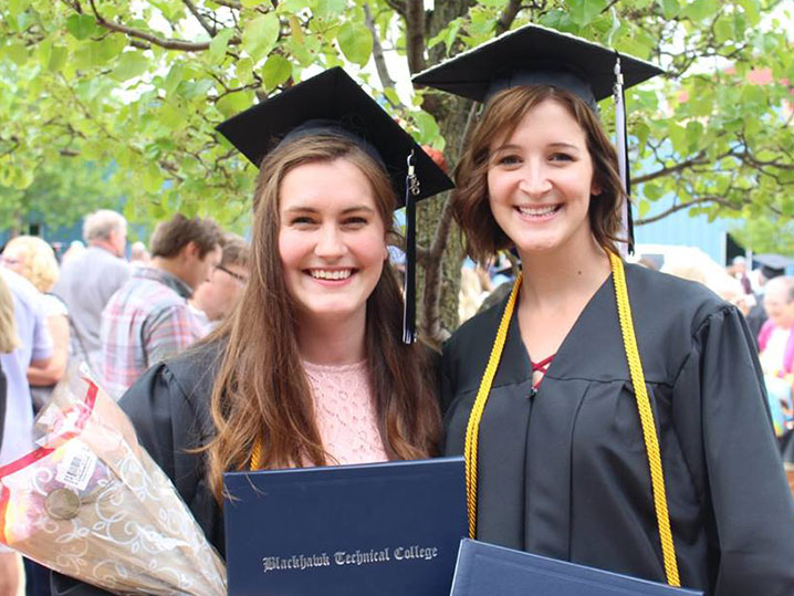 two female graduates standing outside after commencement