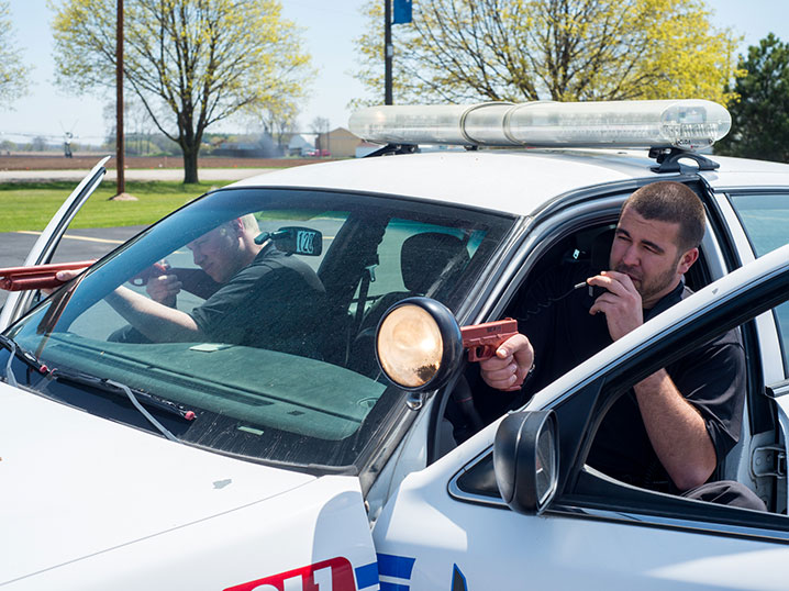 law enforcement academy students practicing skills in squad car
